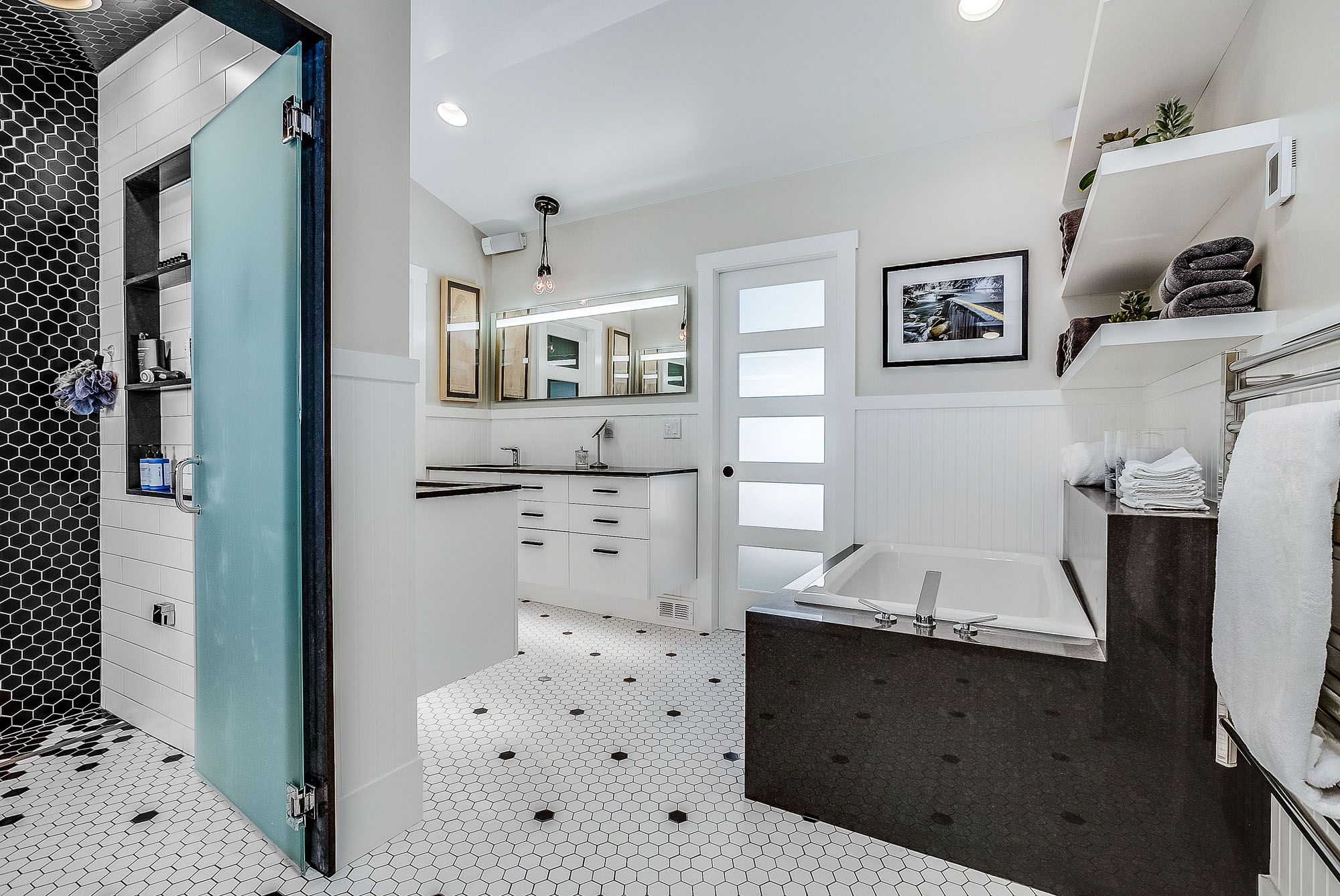 Seventh slide - Black and white master bathroom with tub, vanity and shower room