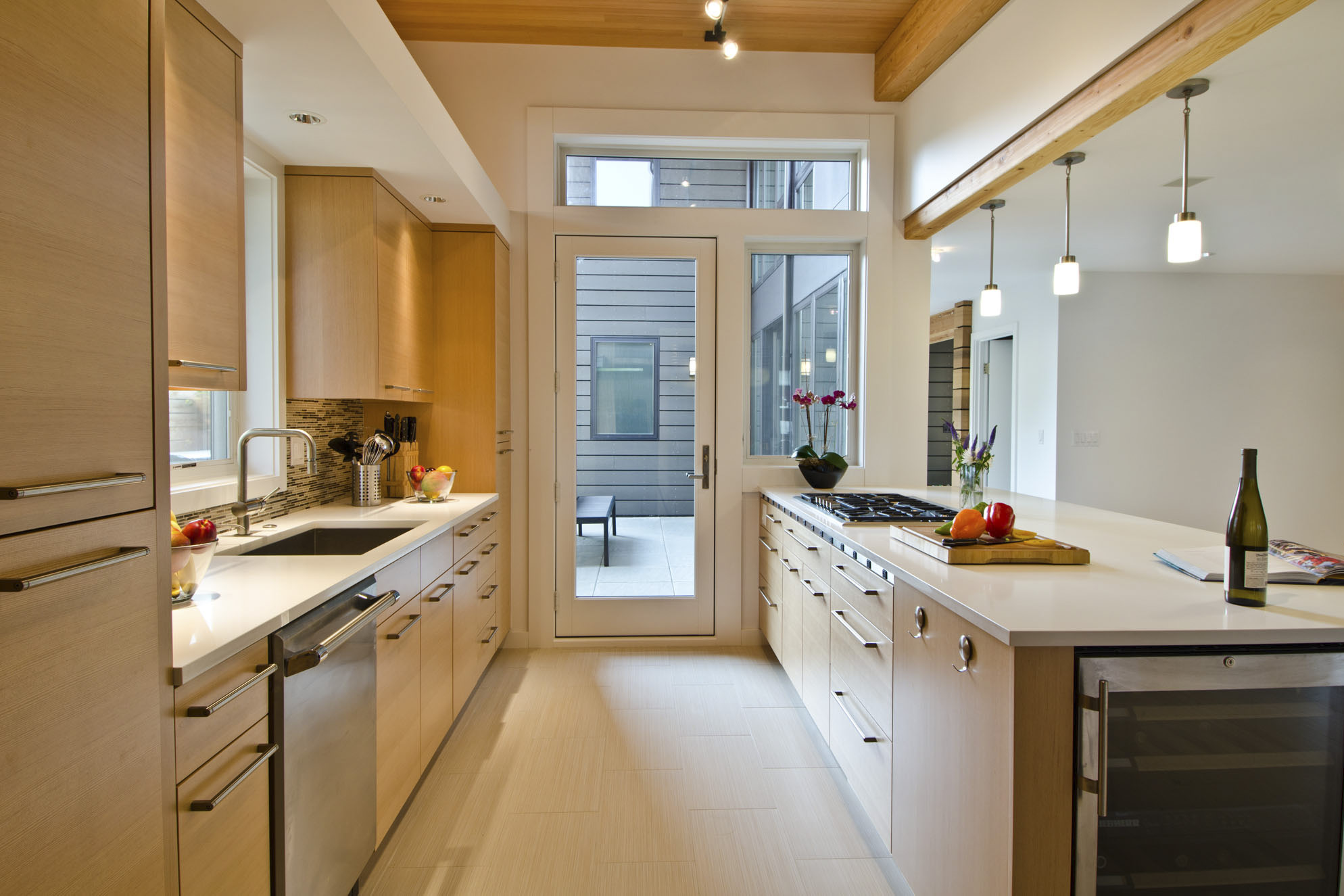 First slide - Modern home galley kitchen with indoor outdoor space and bar seating