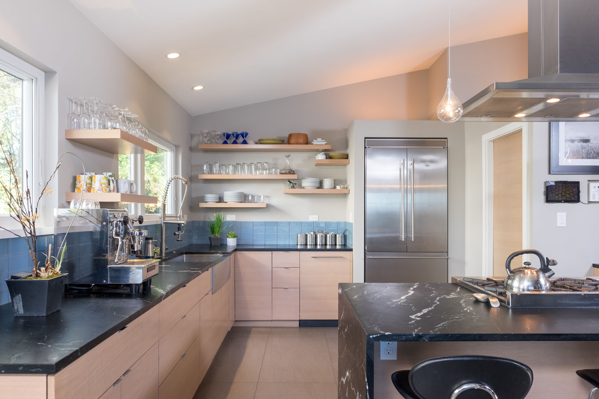 Sixth slide - Modern kitchen with soapstone counters and light wood and tile accents